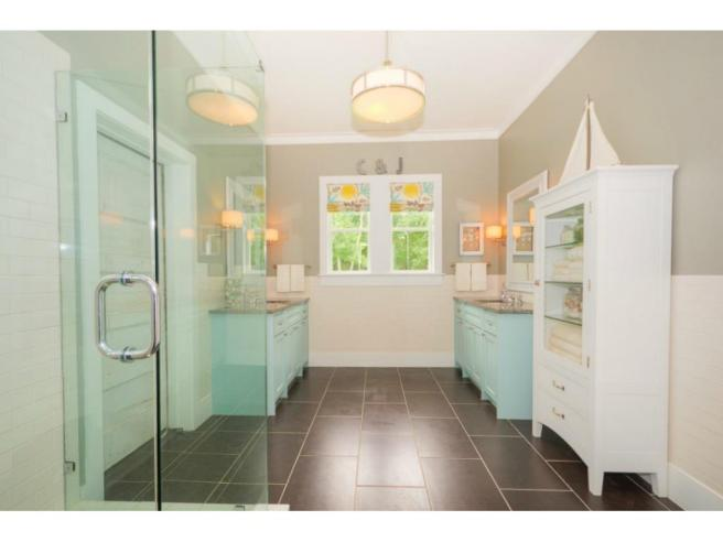 The master bathroom features dual vanities, a large glass shower