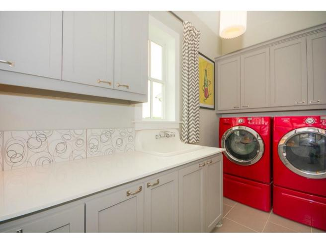 The home also features its own laundry room with a sink and abun